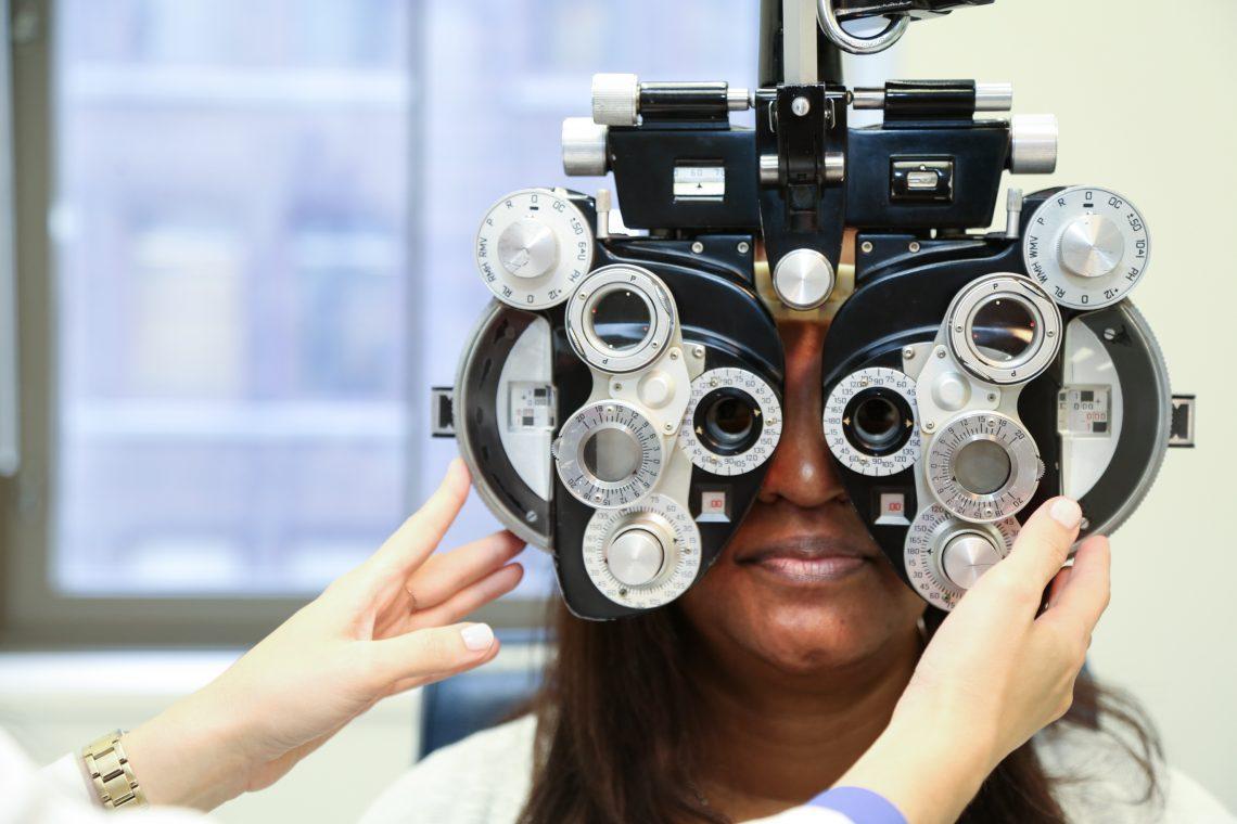 Patient looking throguh eye exam equipment