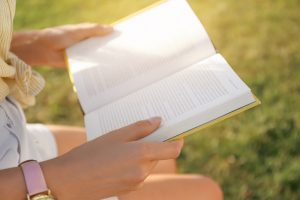 Young woman reading book outdoors on sunny day, closeup