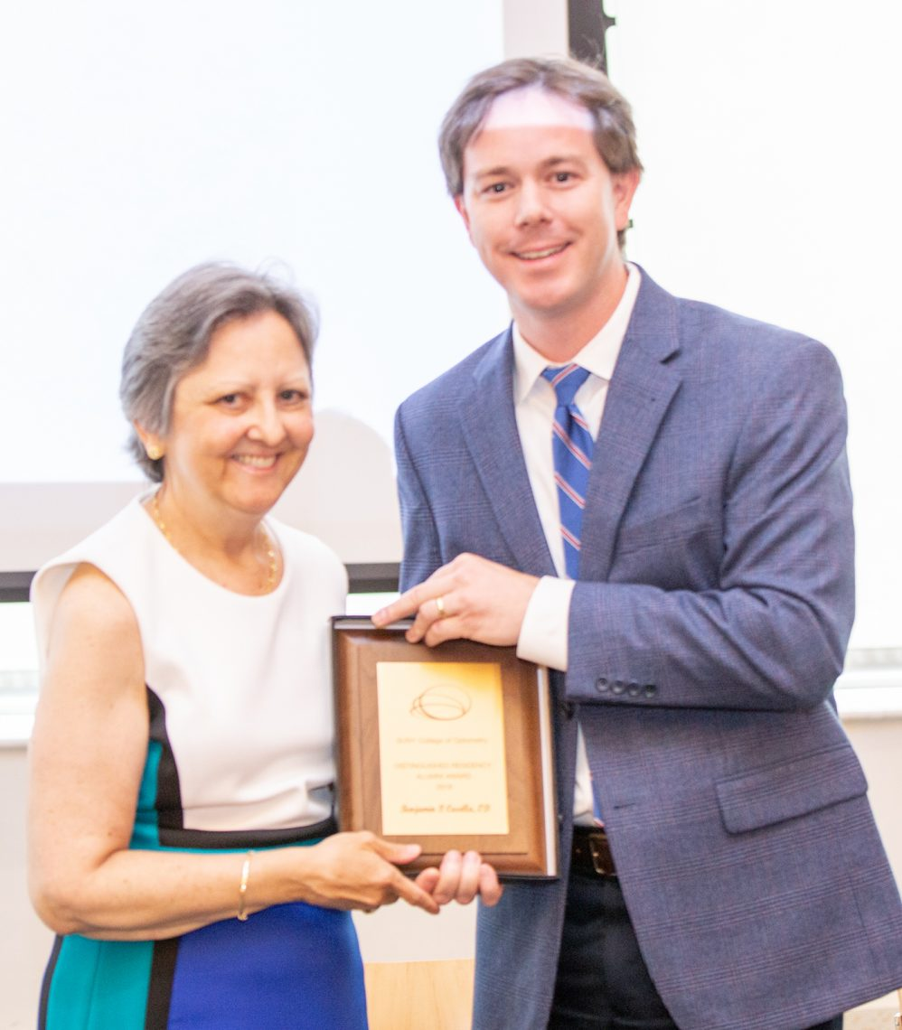 SUNY Optometry director of residency programs Dr. Diane Adamczyk presents Dr. Benjamin Casella with the 2019 Distinguished Residency Alumni Award during the annual Resident's Farewell Reception, June 14, 2019